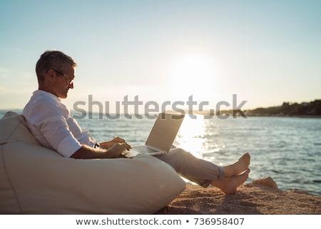 Nyugdíjas férfi vakáció ül napozószék iszik Stock fotó © ivonnewierink