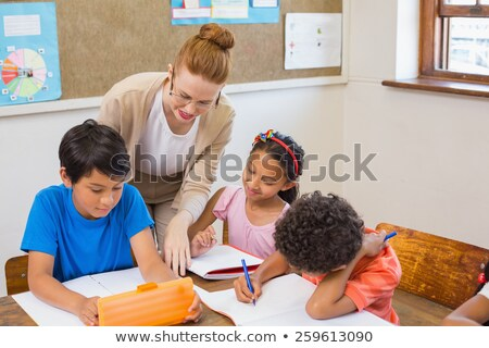 Pretty teacher helping pupil in classroom  Stock photo © wavebreak_media