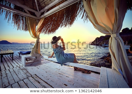 Young woman relaxing at a beachfront resort Stock photo © dash