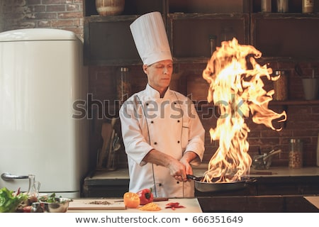 serious chef cook standing and holding frying pan stock photo © deandrobot