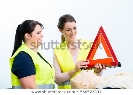 Women in first aid course learning to secure road crash site Stock photo © Kzenon