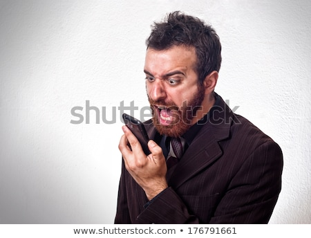 angry bearded man talking on the mobile phone and shouting stock photo © deandrobot