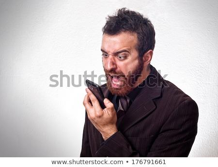 Boos bebaarde man praten mobiele telefoon Stockfoto © deandrobot