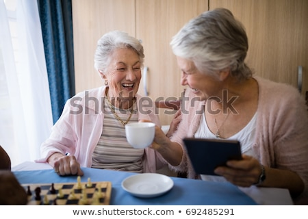 Happy senior friends playing chess while having coffee Stock photo © wavebreak_media