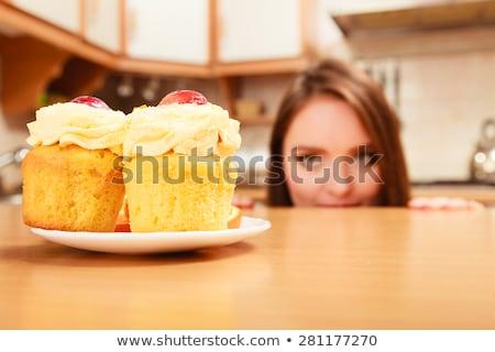 Menina olhando creme bolo cozinha em pé Foto stock © wavebreak_media