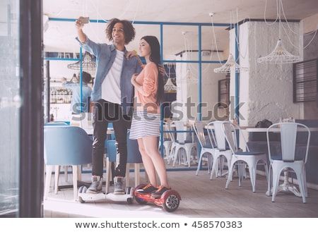 Young couple riding hoverboard - electrical scooter, personal ec Stock photo © vlad_star