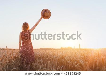 Woman waving hat in field. Stock photo © IS2
