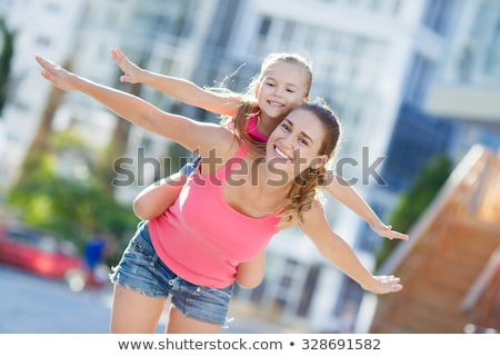 A girl having a piggy back from her mum Stock photo © IS2