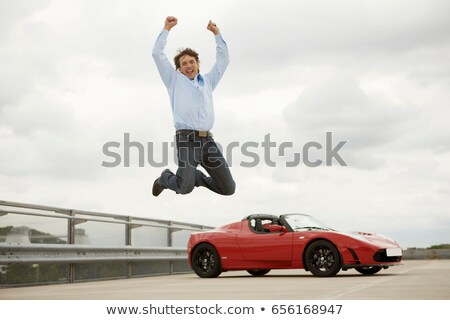 Man jumping happily over electric car Stock photo © IS2
