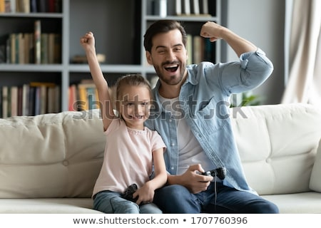 Cheerful gamer playing video games on computer and rejoices Stock photo © deandrobot