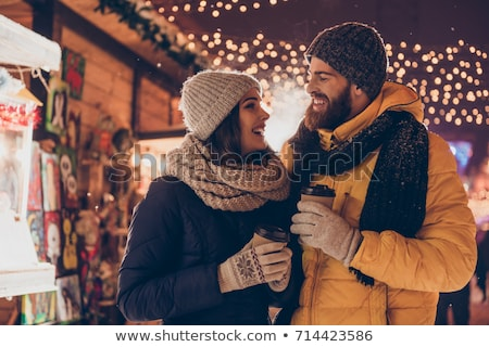 happy young couple with coffee at christmas market stock photo © dolgachov