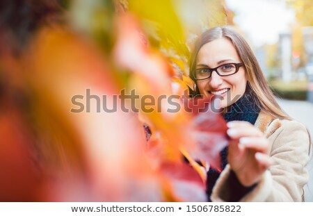 beautiful woman hiding behind red ivy leaves in fall stock photo © kzenon