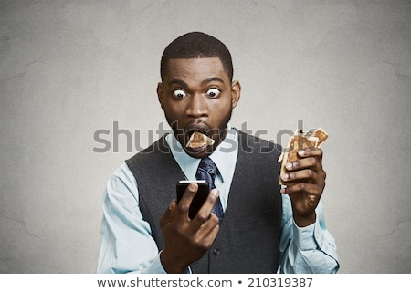 Stock photo: Businessman surprised about text messages on phone.
