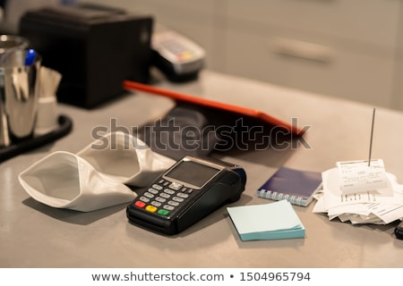 Payment machine, small empty sacks for change, notepapers and stack of receipts Stock photo © pressmaster