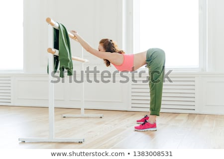 Indoor shot of sportswoman in sportsbra and active wear, leans at ballet barre, has productive train Stock photo © vkstudio