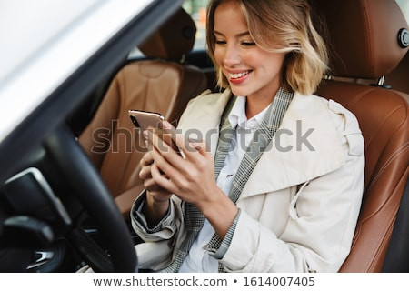 Image of young beautiful businesslike woman sitting in luxury ca Stock photo © deandrobot