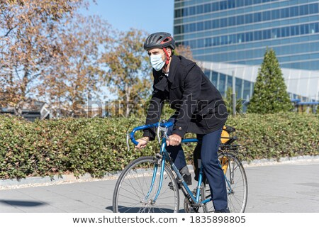 Image of young businessman wearing earphones walking on city str Stock photo © deandrobot