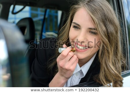 pretty caucasian woman in a car doing makeup stock photo © nobilior