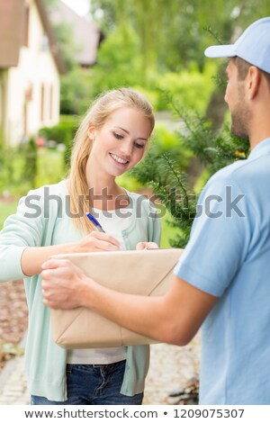 man receiving package from a delivery girl Stock photo © photography33