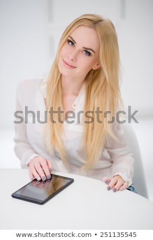 pretty blond woman with tablet gadget at the table stock photo © dash
