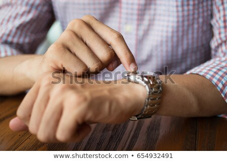 Closeup image of a man pointing on wristwatch Stock photo © deandrobot