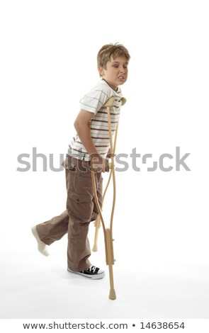 Wincing injured boy using crutches Stock photo © lovleah