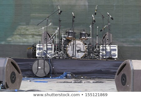 Stock photo: Bright empty scene with microphone, drum set and amplifiers in the light of spotlights