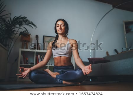 Young woman sitting in lotus yoga pose on mat Stock photo © deandrobot
