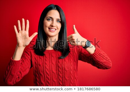 Portrait of smiling young woman wearing sweater while standing against white background Stock photo © wavebreak_media