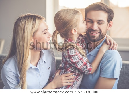 parents kissing daughter on cheeks stock photo © is2