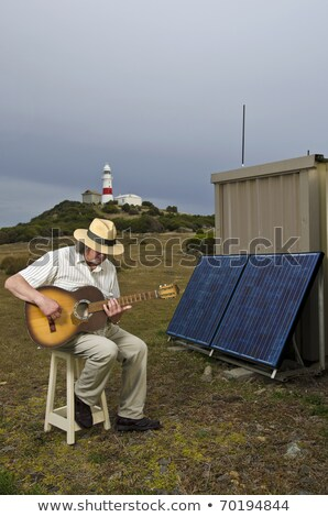 man sitting on stool with electric guitar stock photo © is2
