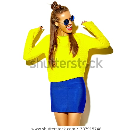A teenage girl in white clothes posing on a yellow background. The girl lowered her jacket to her el Stock photo © Traimak