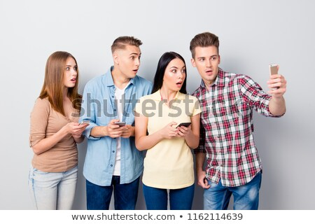 shocked excited group of friends standing isolated stock photo © deandrobot