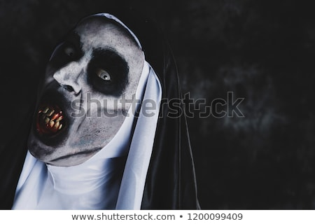 frightening evil nun with bloody teeth