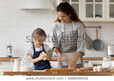 happy mother and daughter baking cookies at home Stock photo © dolgachov