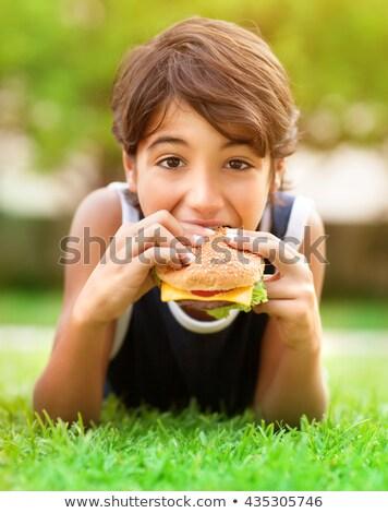 Cute boy is eating big tasty hamburger closeup Stock photo © galitskaya