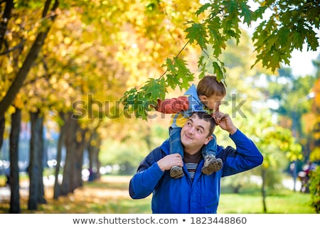 Stock photo: happy father carrying son with autumn maple leaves