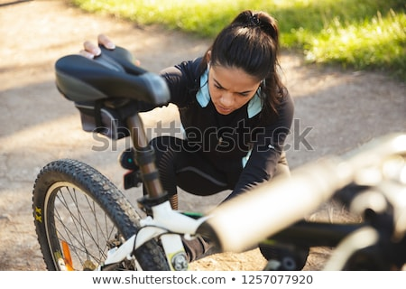 attractive fit sportswoman having to fix her bicycle at the park stock photo © deandrobot