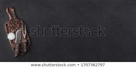 Vintage meat knife hatchets with vintage chopping board and black stone table background. Butcher ut stock photo © DenisMArt