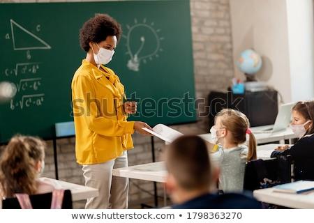 Girl with teacher in classroom. Stock photo © choreograph