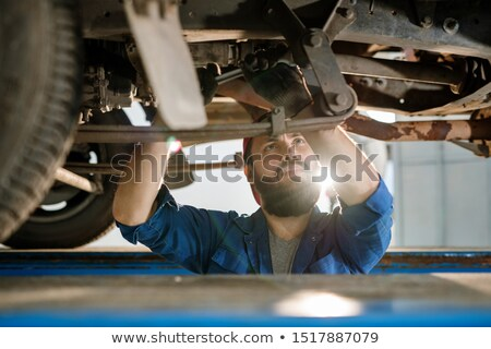 Serious male technical engineer of car repair service looking at one of details Stock photo © pressmaster