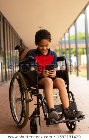 Front view of happy mixed-race disabled schoolboy using mobile phone in corridor at elementary schoo Stock photo © wavebreak_media