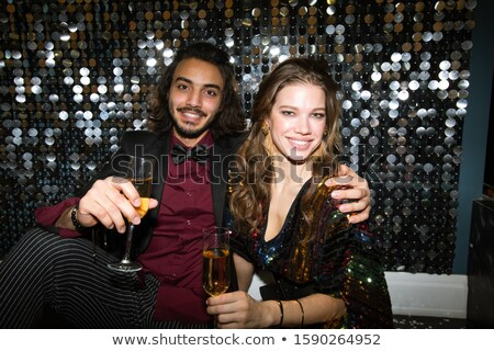 Young affectionate sweethearts with flutes of champagne cheering up at party Stock photo © pressmaster