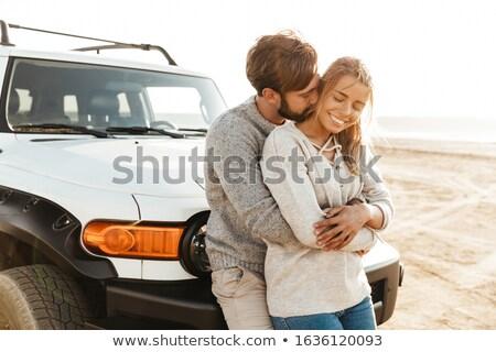 Loving couple outdoors at beach near car hugging. stock photo © deandrobot