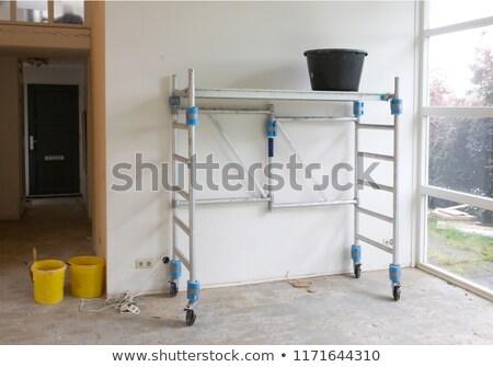 Plasterer standing on scaffolding at construction site Stock photo © Kzenon