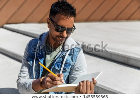 indian man with notebook or sketchbook on roof top Stock photo © dolgachov