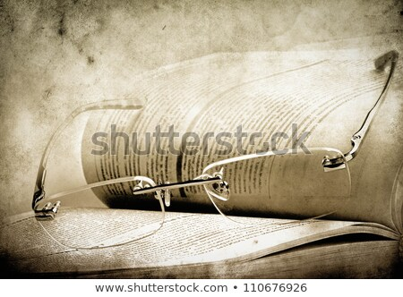 Antique reading glasses on page of bible Stock photo © backyardproductions