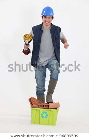 craftsman holding a golden cup and walking over bricks Stock photo © photography33