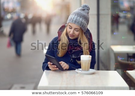 Stockfoto: Young Woman Sitting At A Table Reading Newspaper Holding Latte Macchiato Coffee