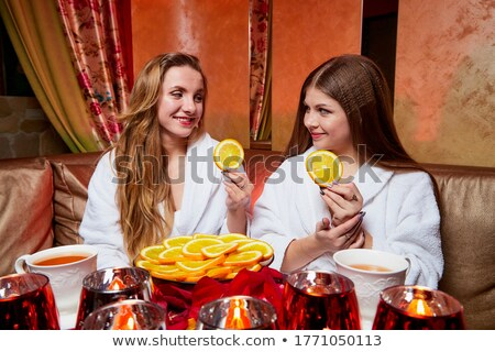 two girls dressed in robes talking in a restaurant Stock photo © photography33
